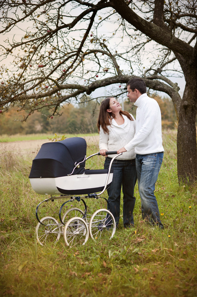 Happy and young family with vintage pram relaxing together in golden and colorful autum nature