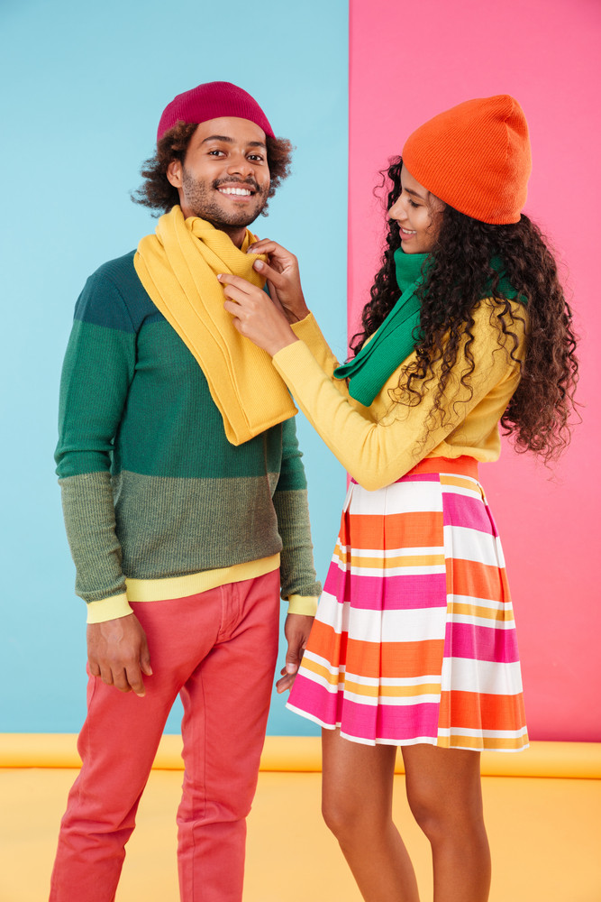 Happy attractive african girl standing and talking care of her boyfriend over colorful background
