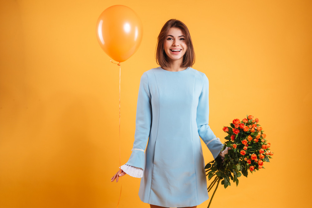 Happy attractive young woman holding bunch of roses and balloon over yellow background