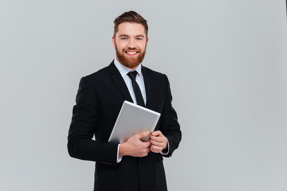 Happy bearded business man in black suit holding tablet computer ...