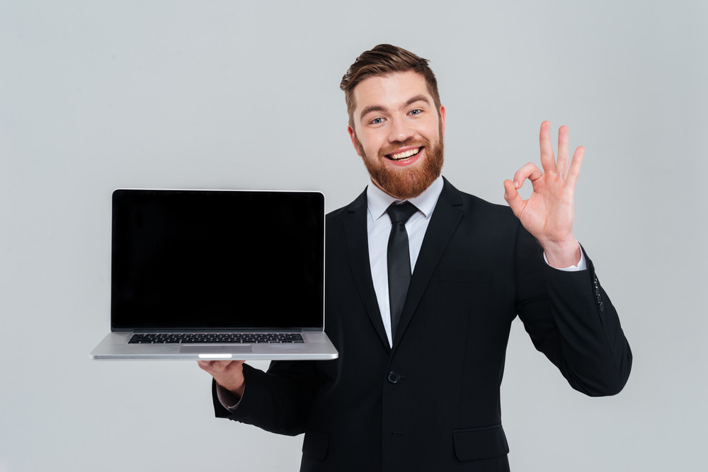 happy bearded business man showing blank laptop screen and showing
