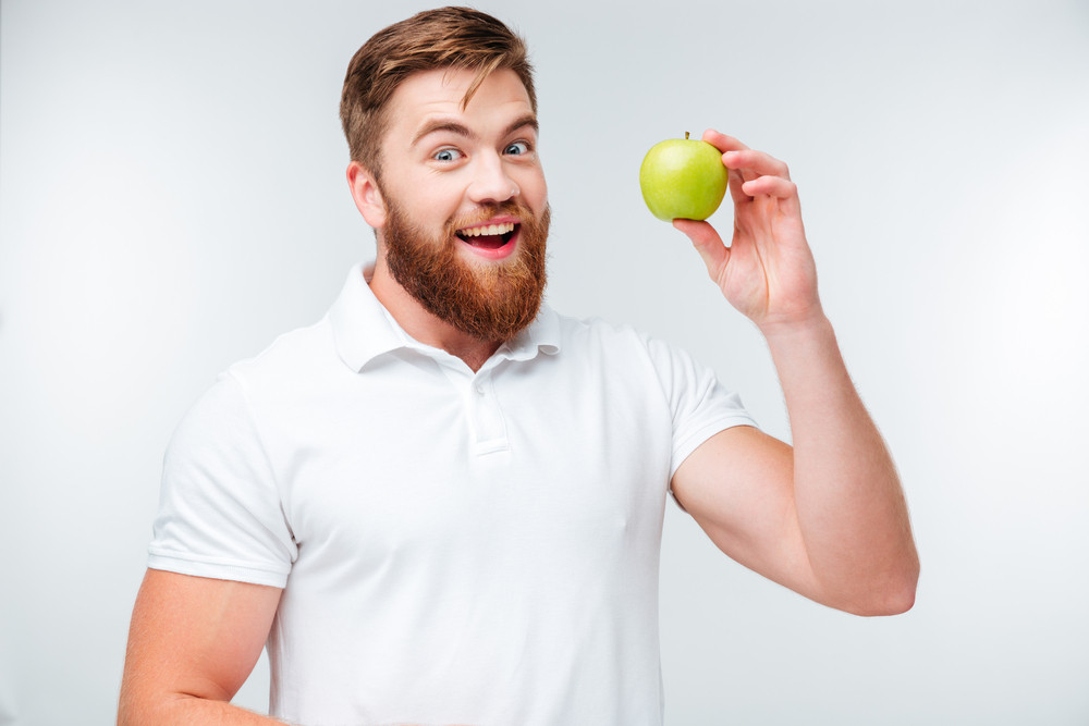 Happy bearded man holding green apple and looking at camera isolated on white background