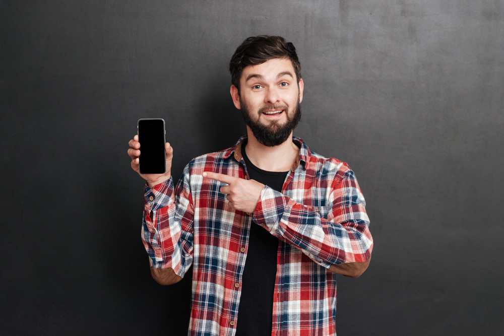 Happy bearded young man in plaid shirt holding and pointing on blank screen mobile phone over grey background