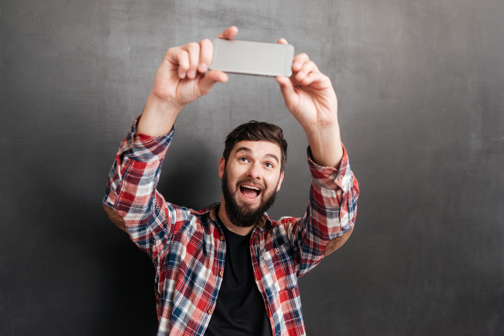 Happy bearded young man in plaid shirt making selfie with mobile phone over grey background