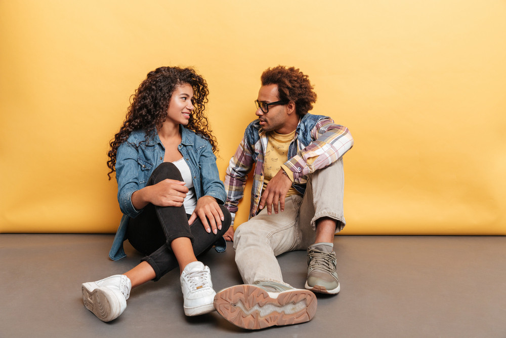 Happy beautiful african american young couple sitting and talking together over yellow background