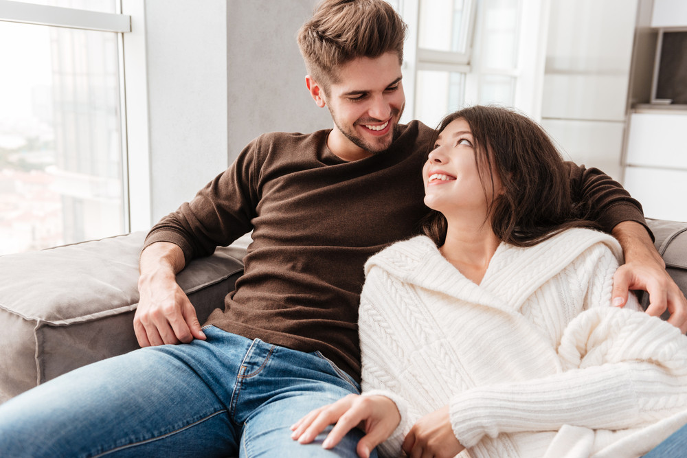 Happy beautiful young couple sitting on sofa at home together
