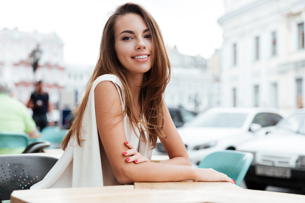 Happy beautiful young woman sitting in outdoor cafe