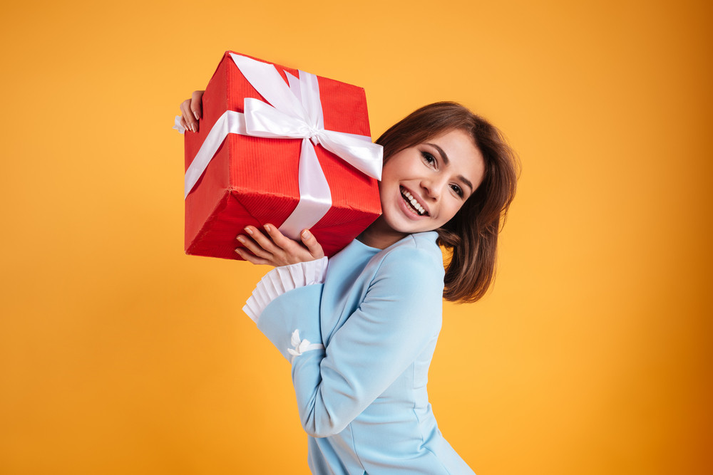 Happy beautiful young woman standing and holding present box over yellow background