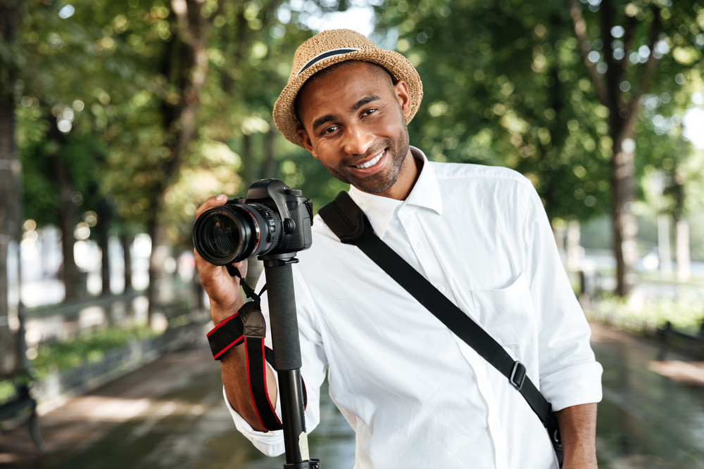 Happy black man in park with camera and hat