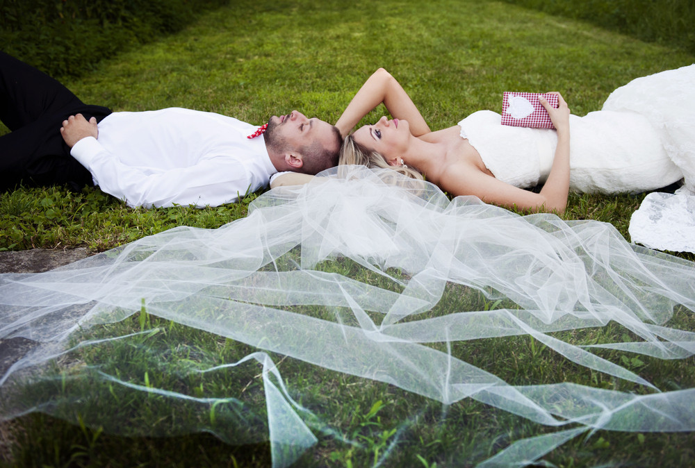 Happy bride and groom enjoying their wedding day in green nature, lying on grass