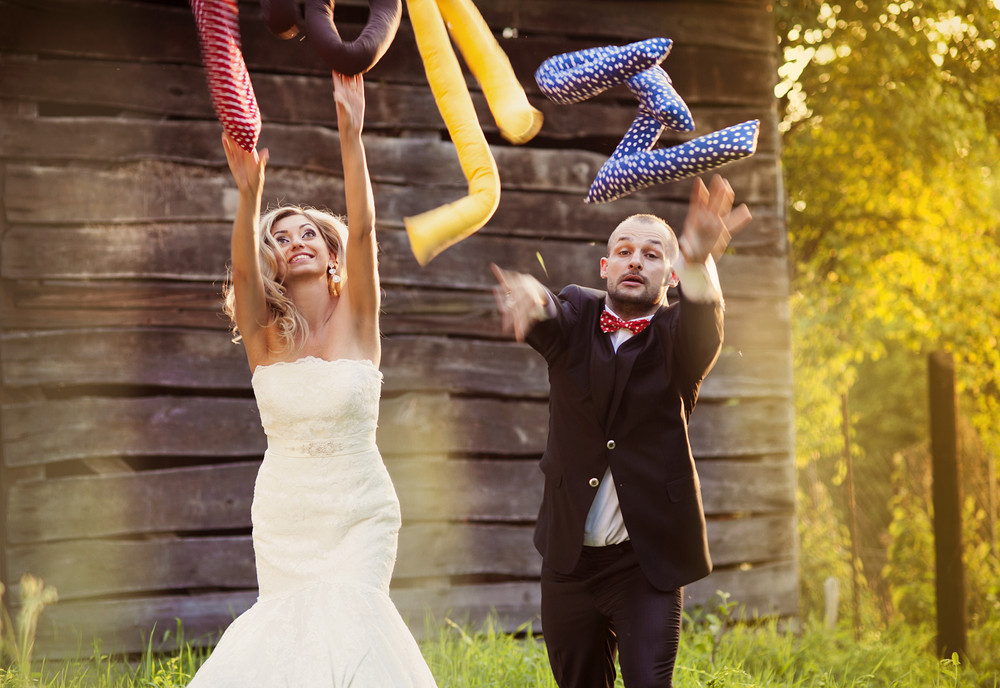 Happy bride and groom on their wedding day having fun with love cushions outside in the garden