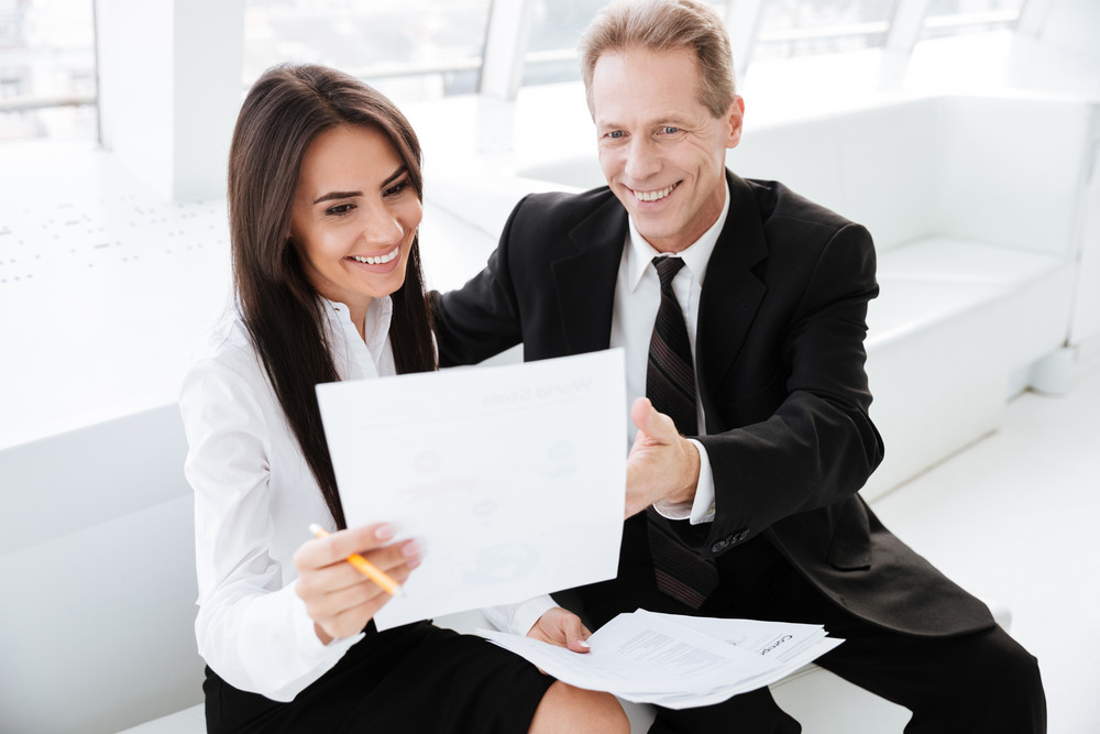 Happy Business people sitting on sofa and looking at documents in office