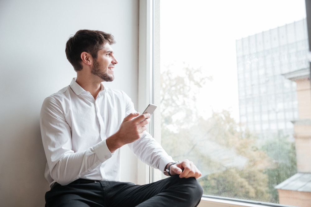 Happy businessman dressed in white shirt sitting in cafe and look at window while chatting by phone