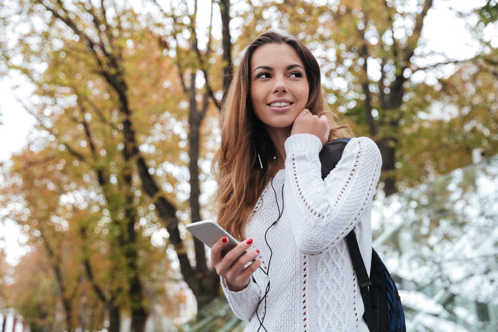 Happy charming young woman with earphones listening to music from cell phone outdoors