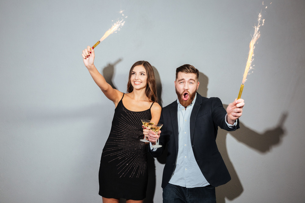 Happy cheerful couple celebrating holding glasses with champagne and petards over gray background