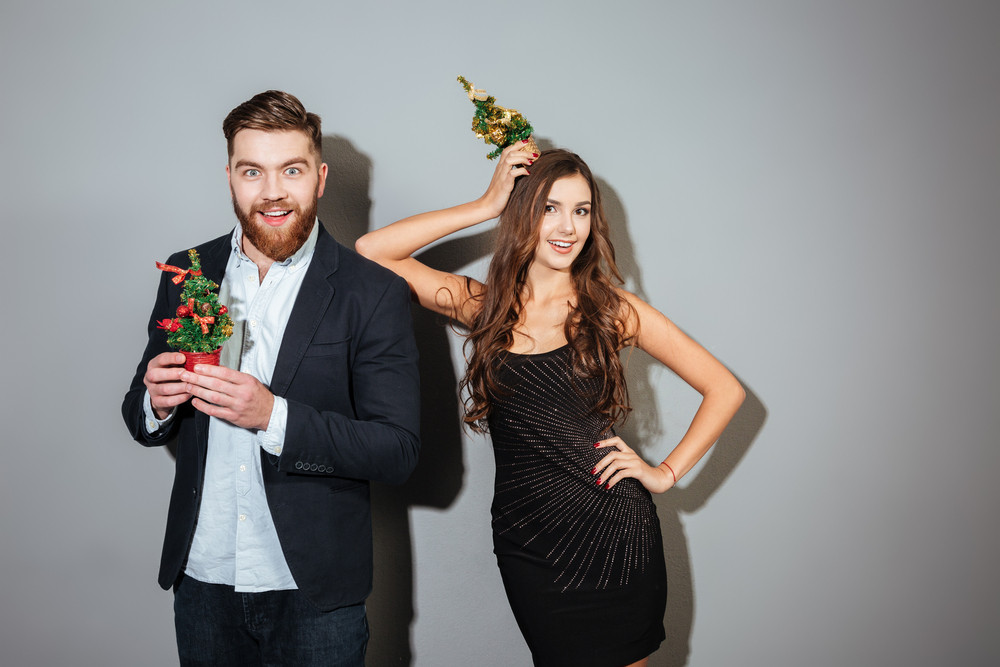 Happy cheerful couple in smart wear celebrating christmas together over gray background