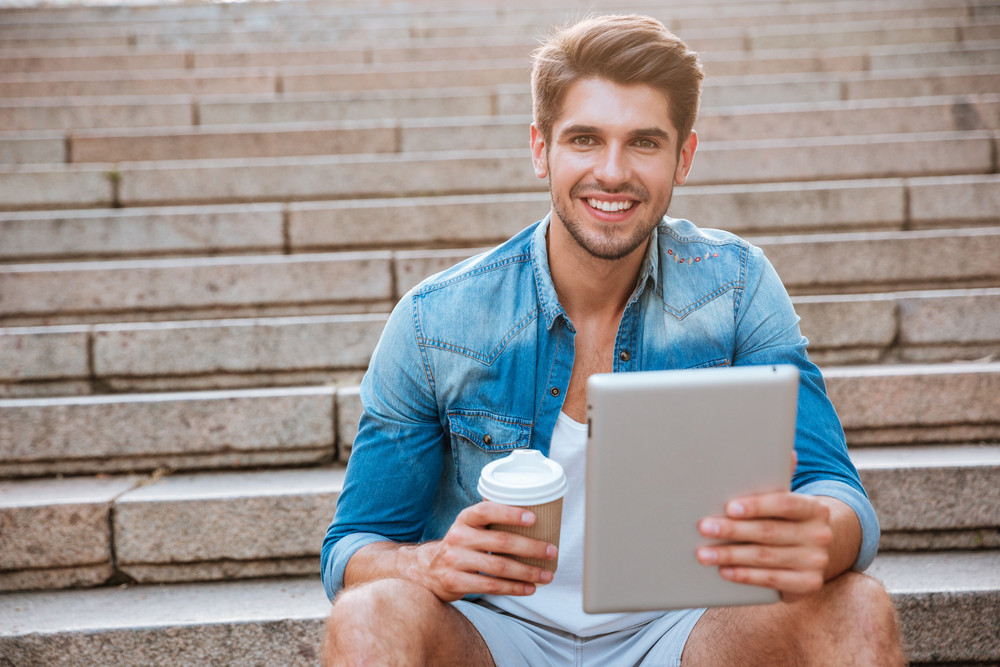 Happy cheerful student with tablet and coffee cup sitting on the staircase outdoors