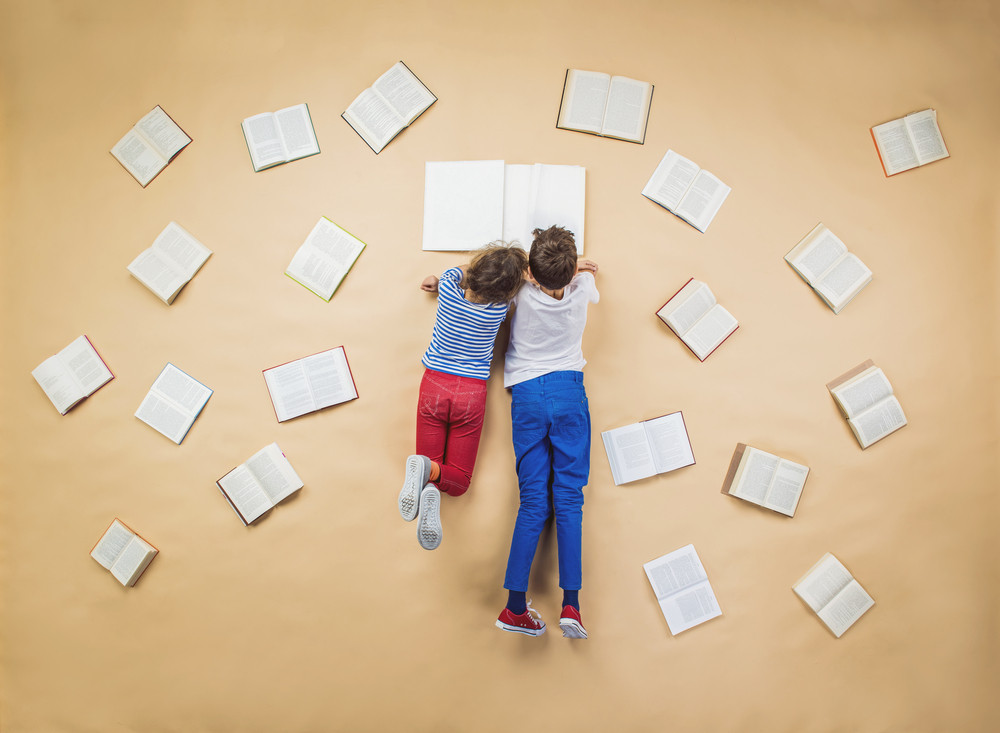 Happy children are reading book on the floor with group of books around them