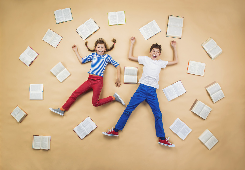 Happy children lying on the floor with group of books