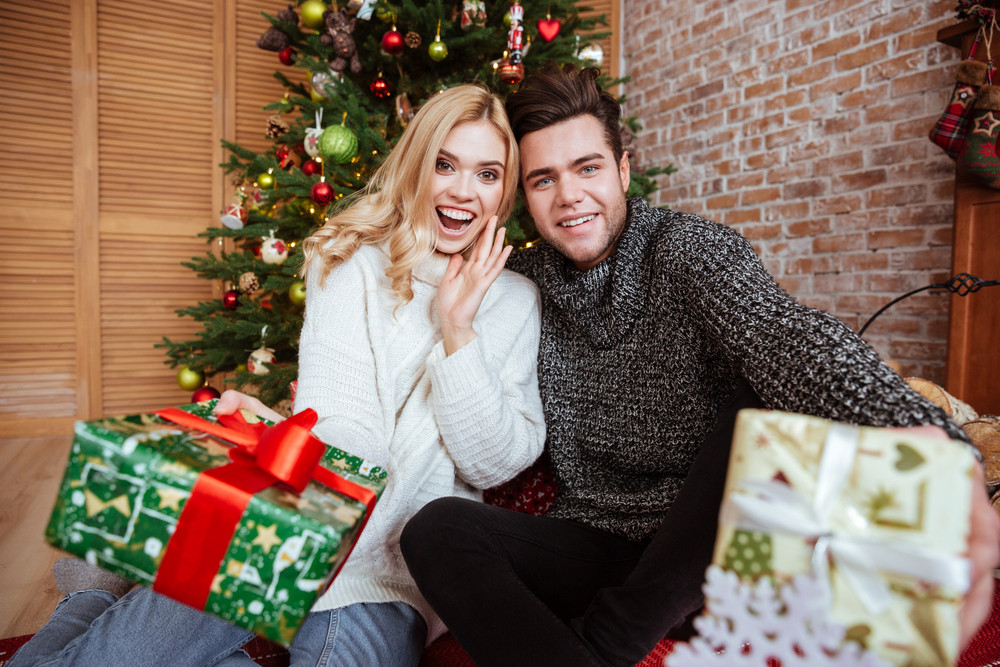 Happy couple in sweaters sitting on the floor with gifts near the fir-tree