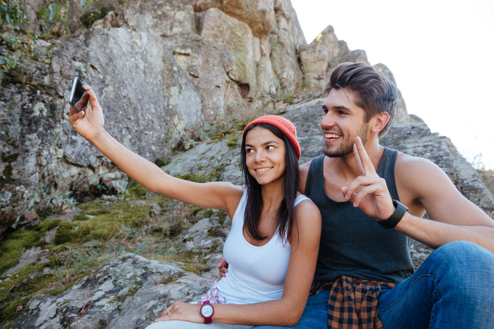 Happy couple make selfie and sitting on rock. girl holding the phone