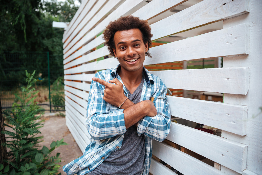 Happy curly african young man standing outdoors and pointing away