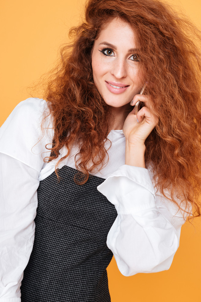 Happy curly young woman smiling and talking on cell phone