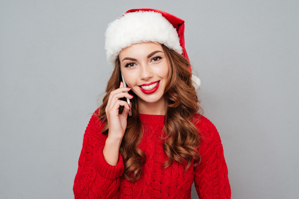 Happy cute girl in santa hat talking on cell phone