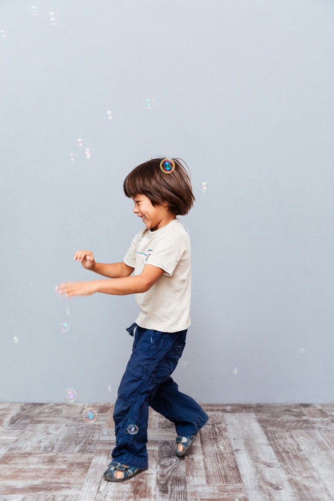 Happy cute little boy playing with soap bubbles over gray background