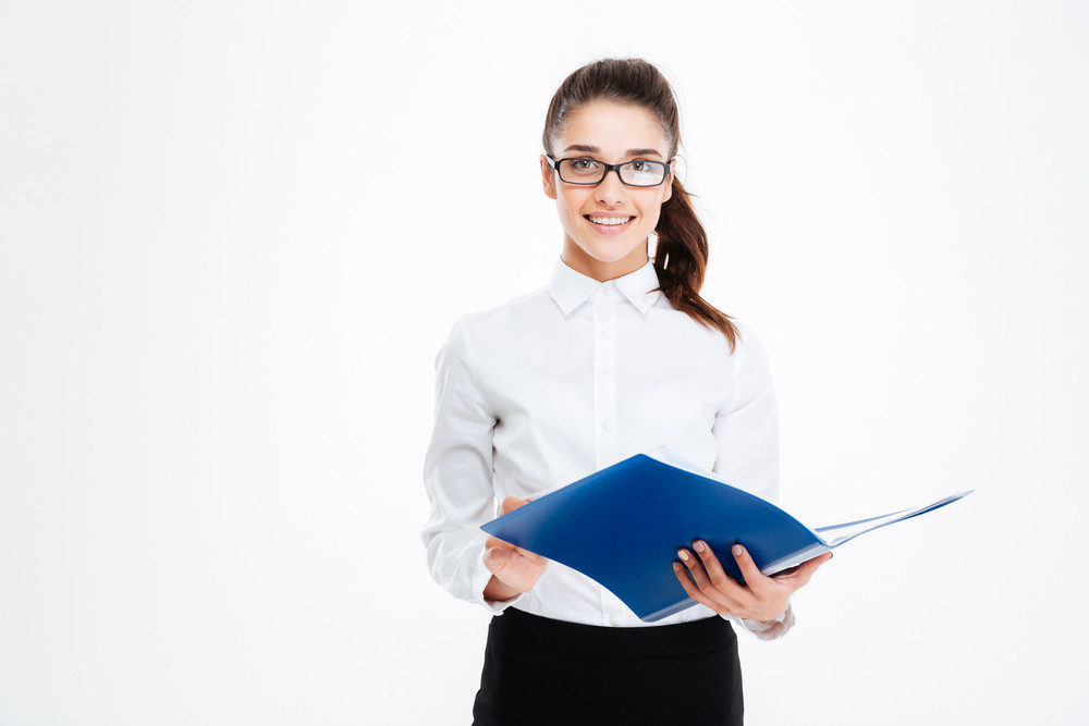 Happy cute young business woman in glasses standing and holding folder over white background