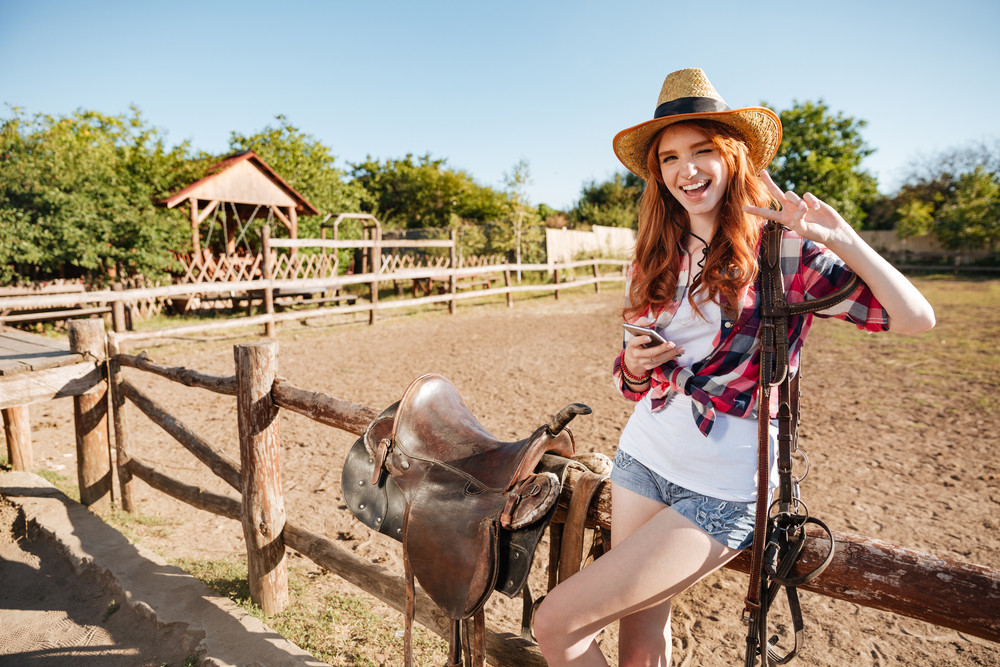 Happy cute young woman cowgirl with cell phone standing and showing peace sign