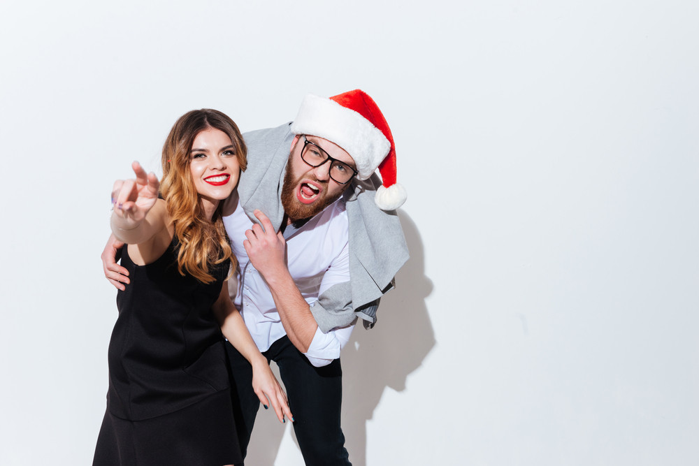 Happy drunk young couple in santa hat standing and shouting over white background
