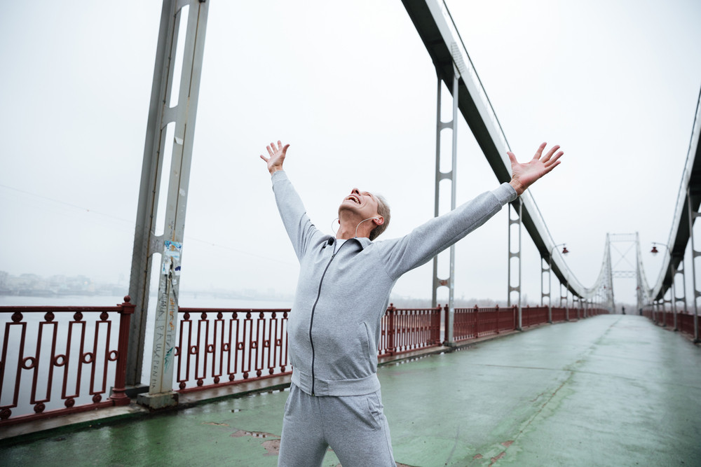 Happy elderly man in gray sportswear standing on bridge with hands up looking up