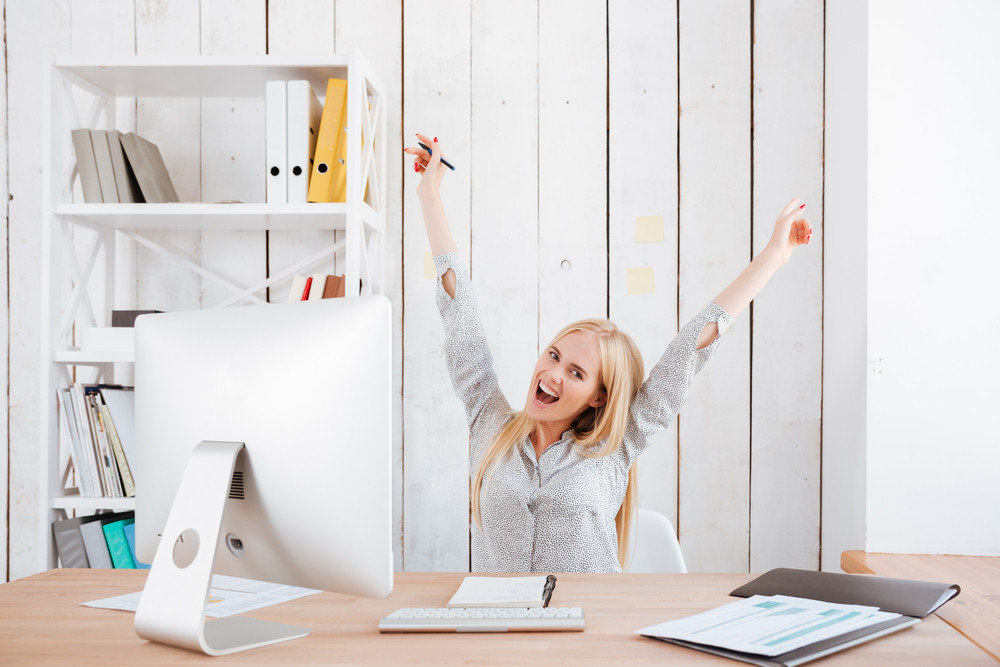 Happy excited business woman celebrating success while sitting at her workplace with hands raised
