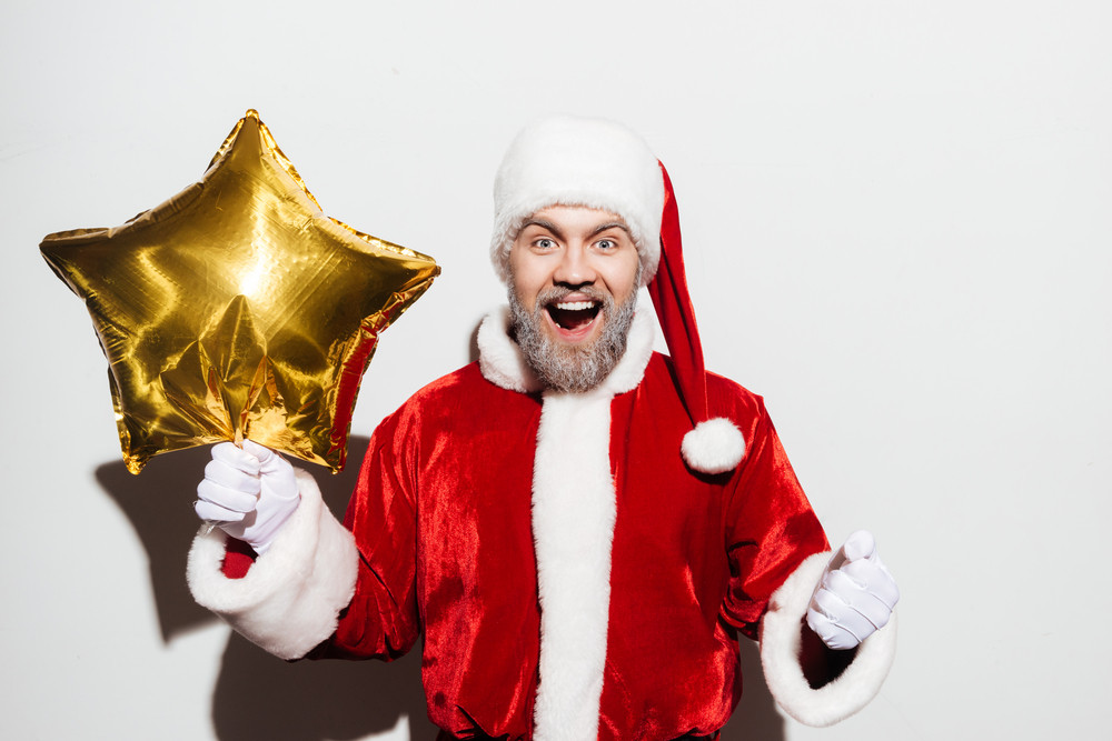 Happy excited man santa claus holding golden star shaped balloon and shouting