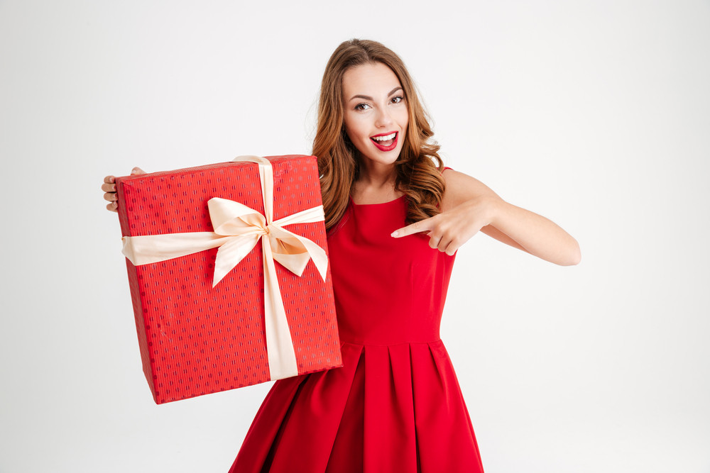Happy excited woman in red dress pointing finger at big gift box isolated over white background