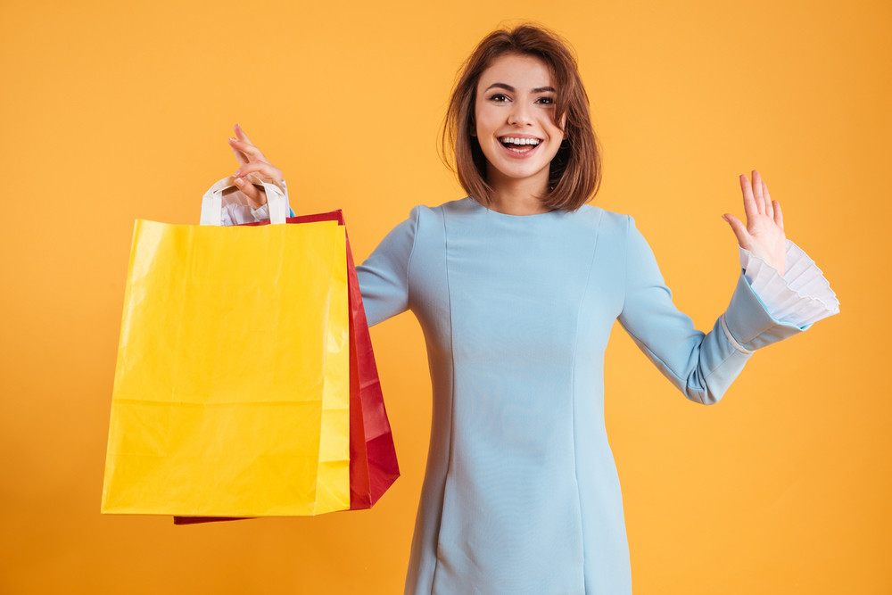 Happy excited young woman smiling and holding shopping bags over yellow background