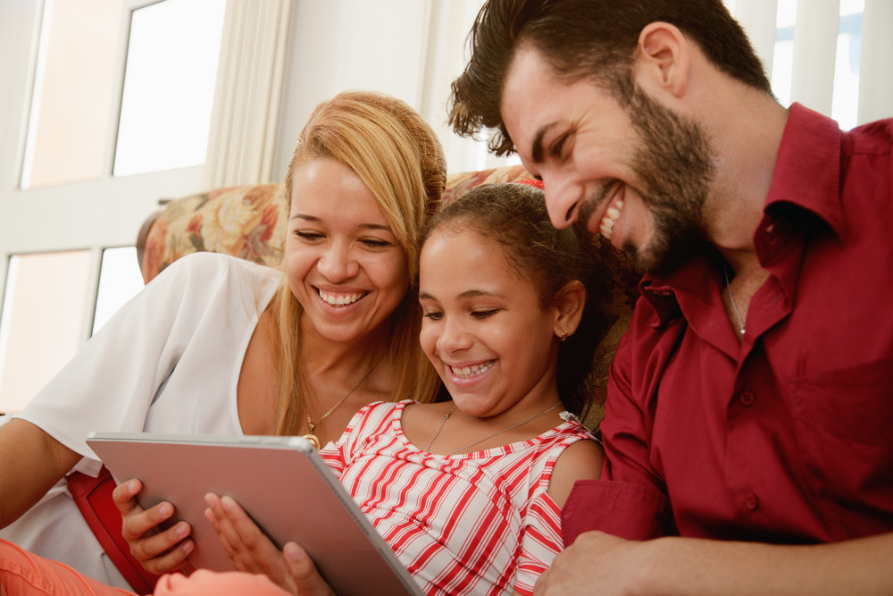 Happy family at home. Mother, father and child with playing with tablet PC. Hispanic mom, dad and daughter having fun looking at photo and video on digital display.