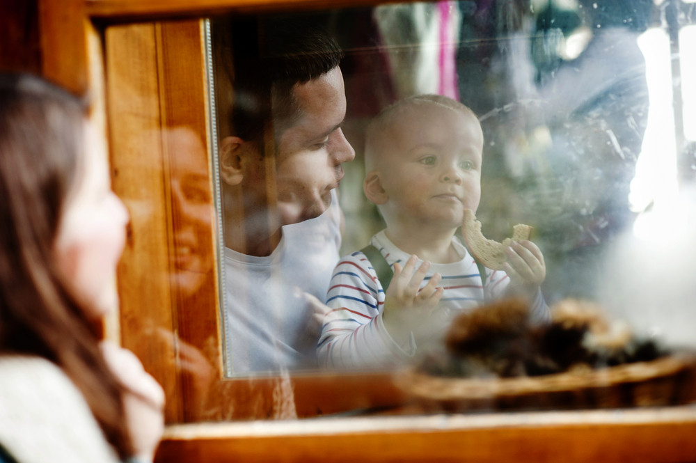 Happy family is enjoying time together. mother is outside looking through the window to her husband and liitle son