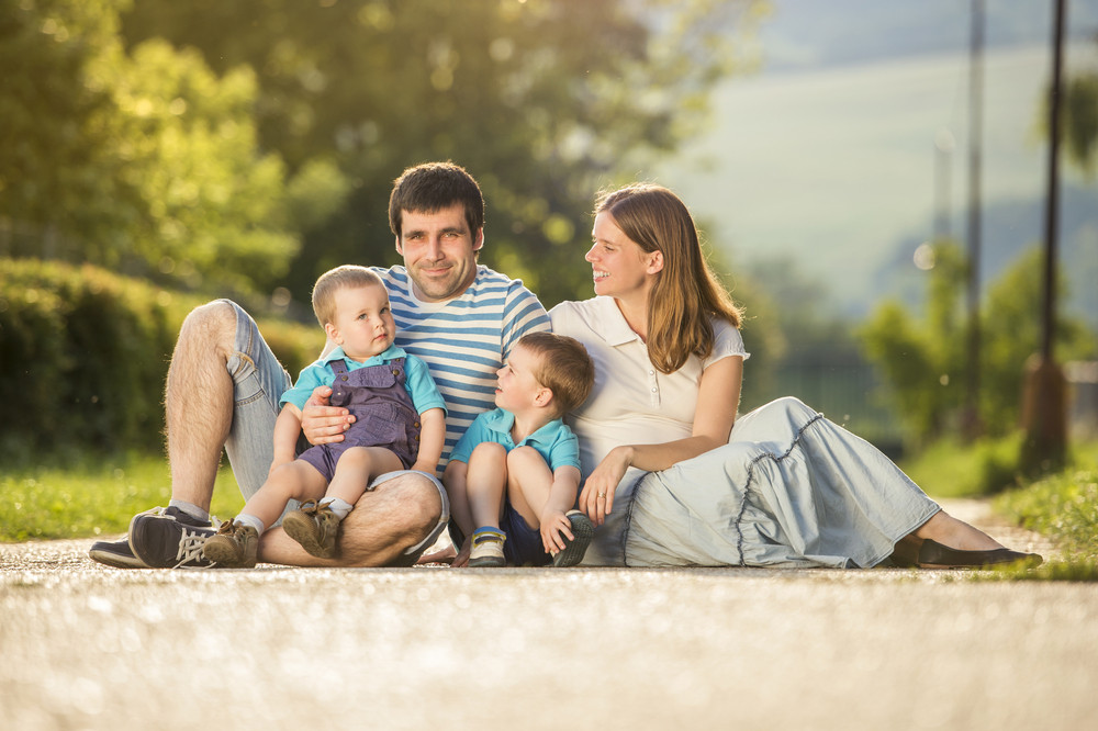 Happy family is relaxing and sitting on countryside road