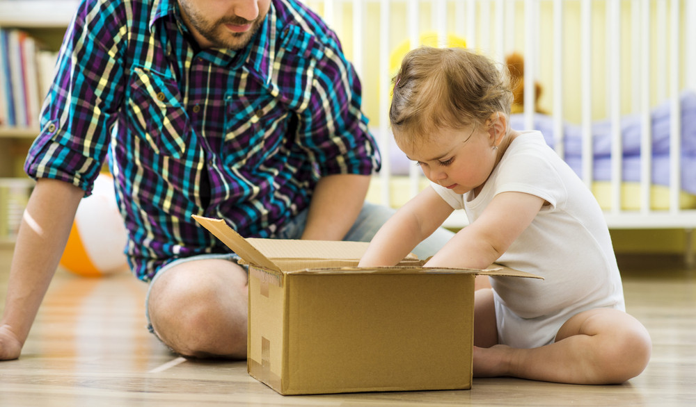 happy father and his little daughter opening box