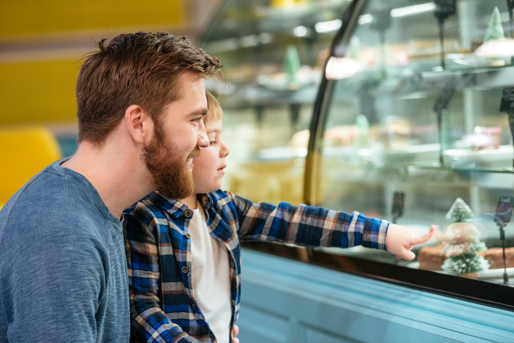 Happy father and little son choosing cake in showcase at supermarket