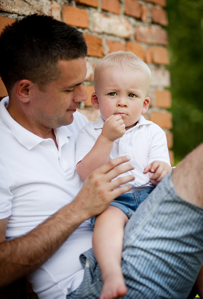 Happy father with little son spending time in nature by the old house