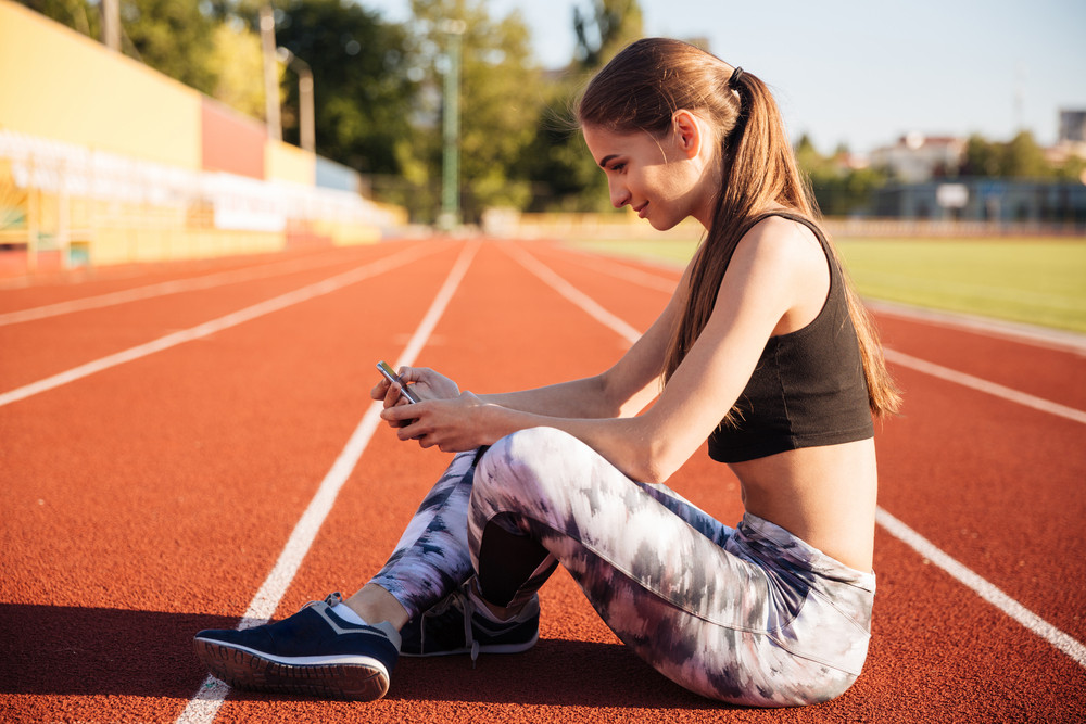 Happy female athlete using mobile phone on running track at the stadium
