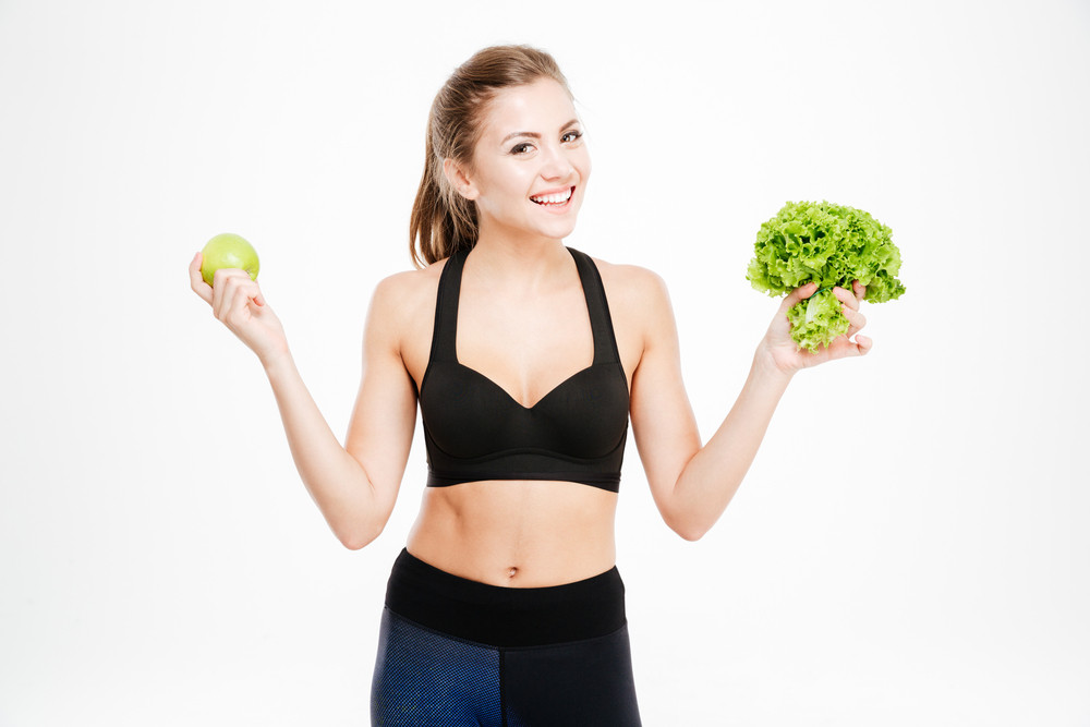 Happy fitness woman holding apple and lettuce and looking at camera isolated on a white background