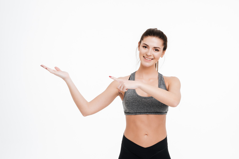 Happy fitness woman pointing finger at copyspace on her palm isolated on a white background