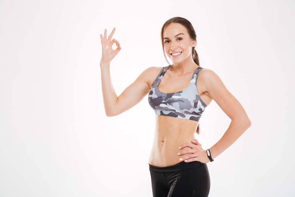 Happy fitness woman. showing ok. looking at camera. isolated white background