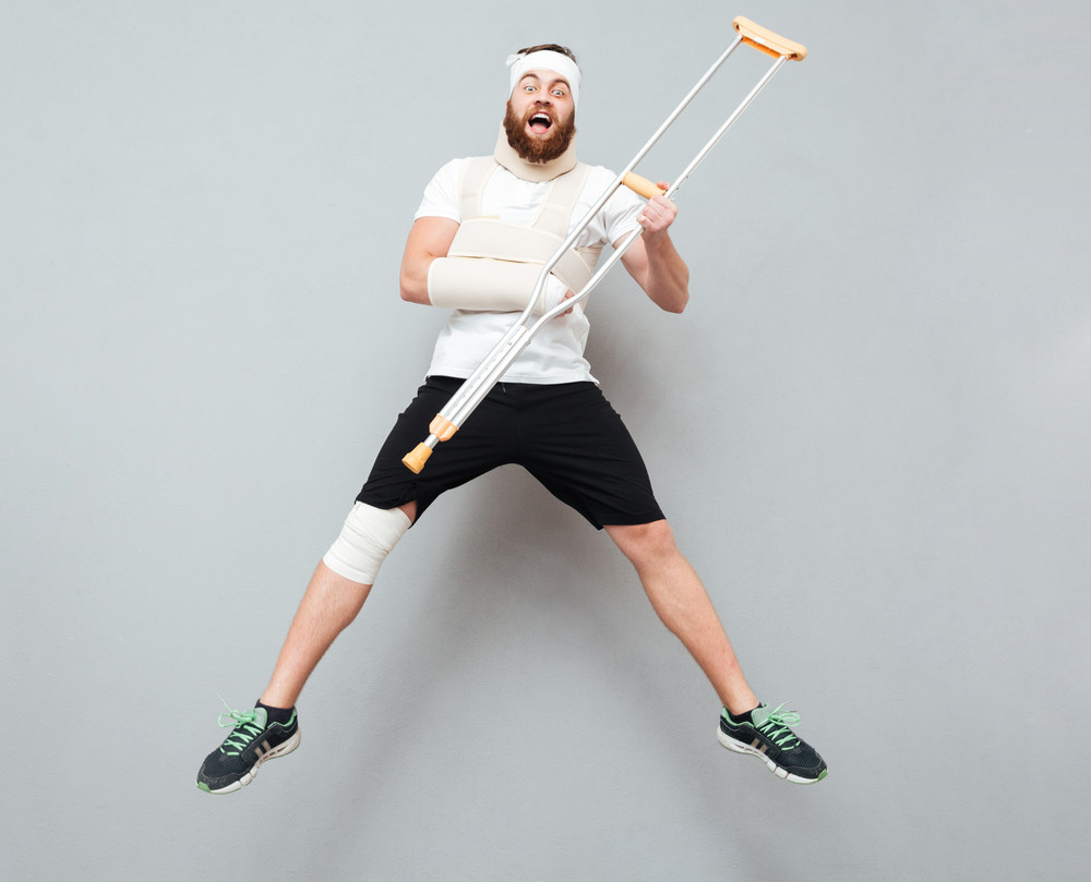 Happy funny young man jumping and having fun with crutch over gray background