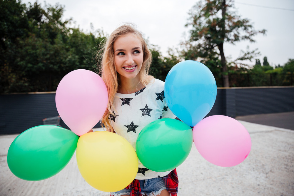 Happy girl holding bunch of colorful air balloons outdoors