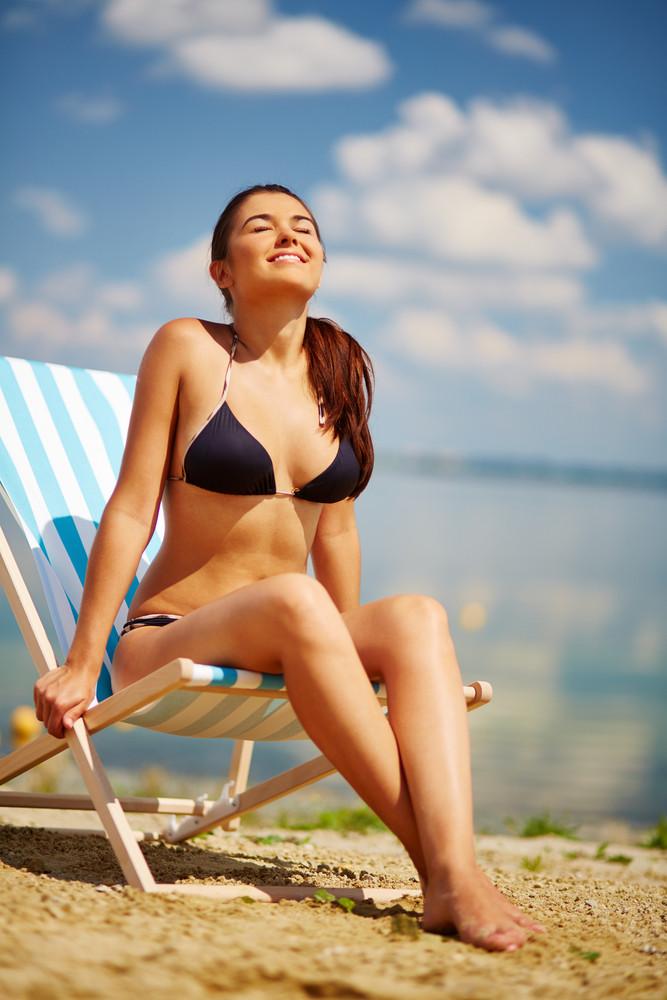 Happy girl in bikini sunbathing on the beach
